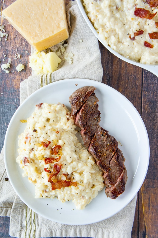 a white plate with steak and cheesy rice over a gold striped napkin with a block of parmesan