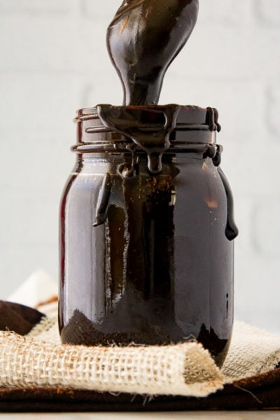 a jar of fudge sauce with a spoon lifting fudge out
