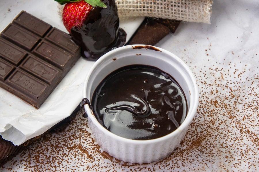 a small white ramekin of fudge sauce next to dark chocolate and strawberries