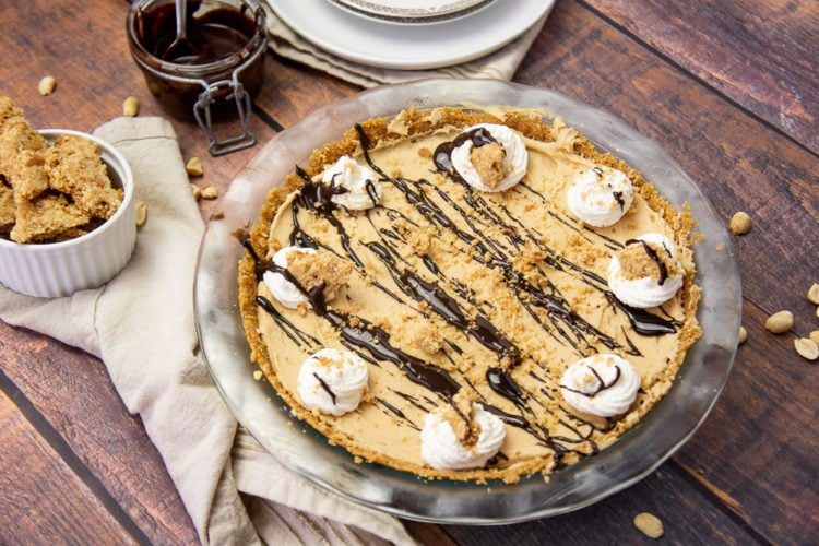 a frozen peanut butter pie topped with whipped cream, chocolate sauce, and peanut butter crumbles