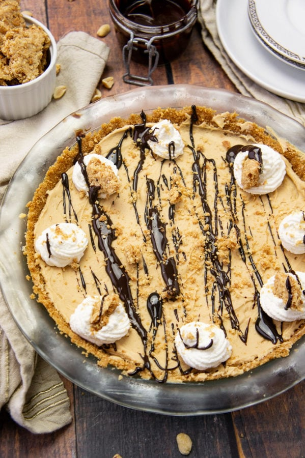 a peanut butter pie with chocolate sauce and whipped cream in a glass pie plate