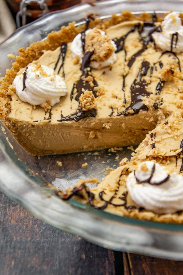 a close up of frozen peanut butter pie in a glass pie plate with a slice removed
