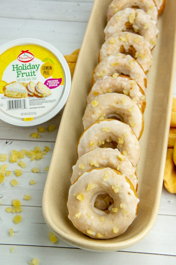 a long tray with glazed baked lemon donuts stacked in it beside a container of candied lemon peel