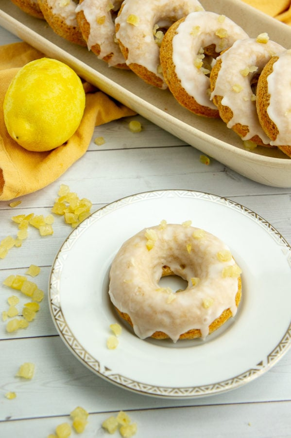 a single baked lemon donut on a plate with a row of donuts on a platter behind it