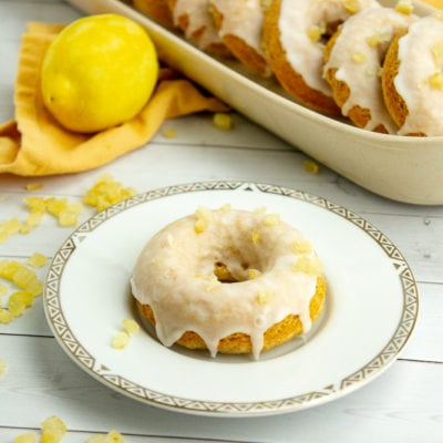 a small plate with a single donut on it in front of a tray of donuts and a lemon