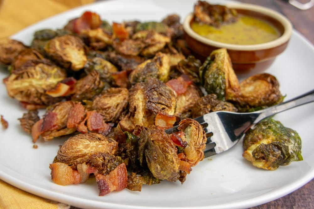 a white platter with fried brussel sprouts and bacon