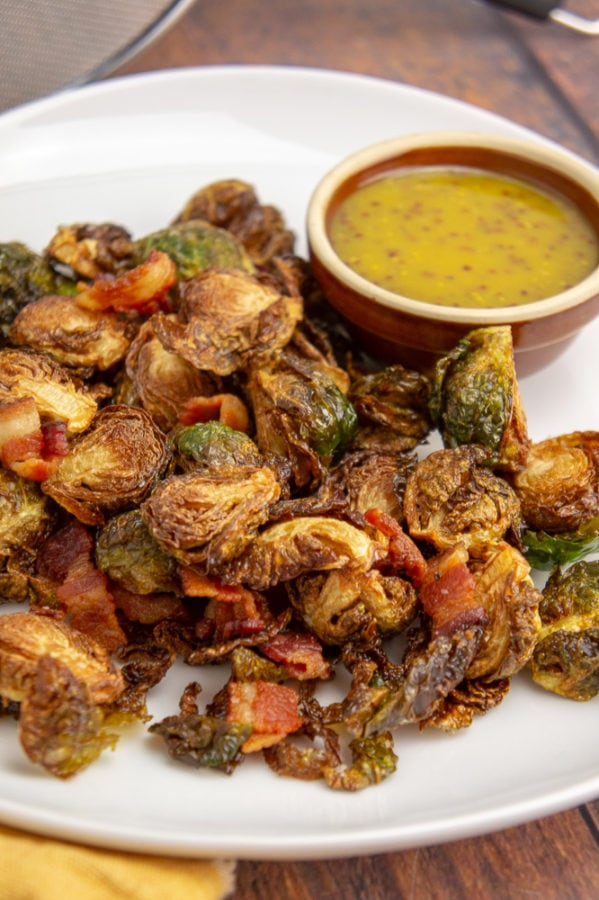 a white platter with deep fried brussels sprouts with a brown bowl of yellow mustard dressing