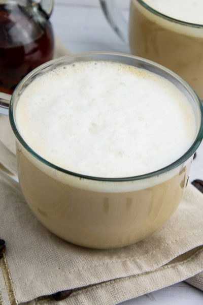 a creamy homemade latte in a glass cup on a beige napkin
