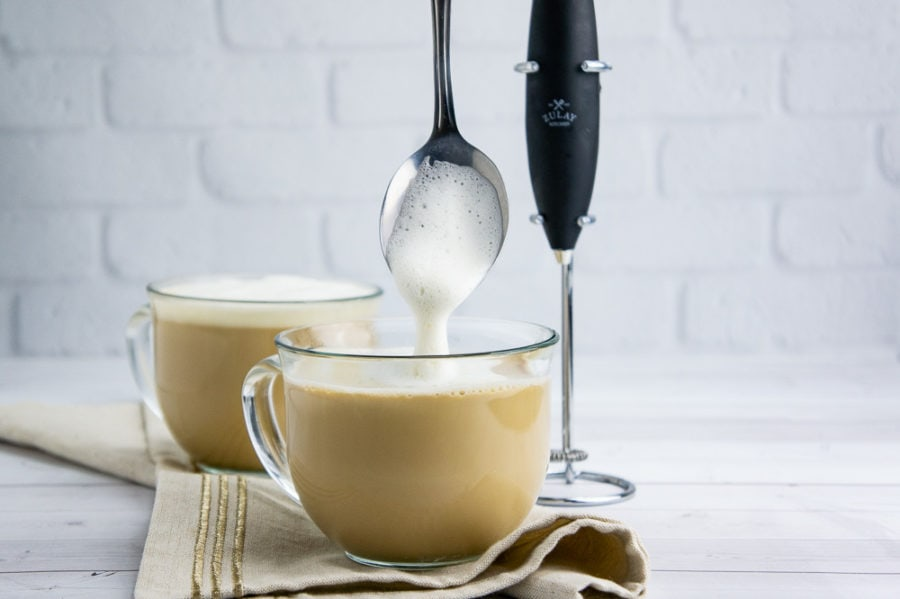 foam being ladled into a clear glass coffee cup with a latte in it
