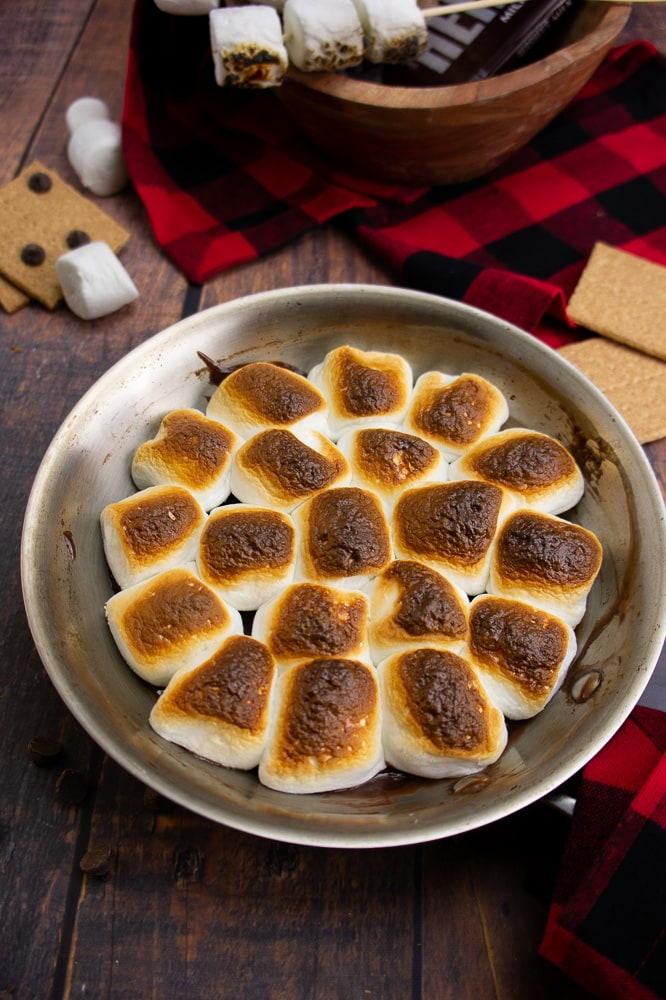 a pan with oven s'mores dip on a wooden table with a red and black checkered napkin and graham crackers