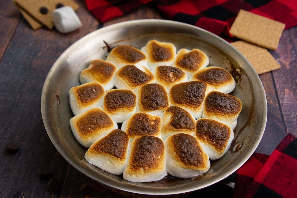 a pan with oven s'mores dip on a wood surface with a red and black checked napkin