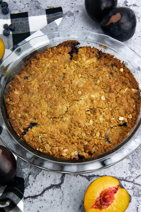 a golden brown plum and blueberry cobbler on a stone surface