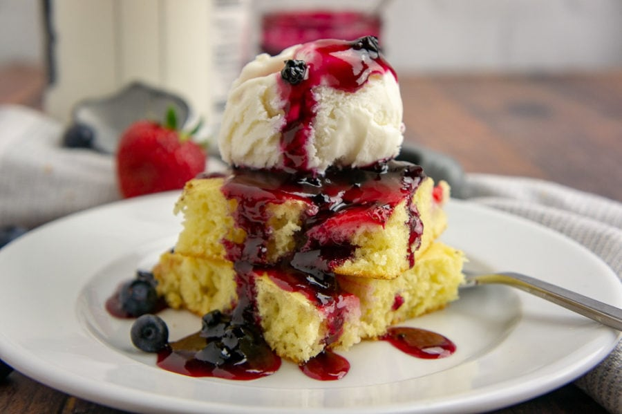 two fluffy baked pancake squares stacked on top of each other and topped with ice cream and blueberry syrup