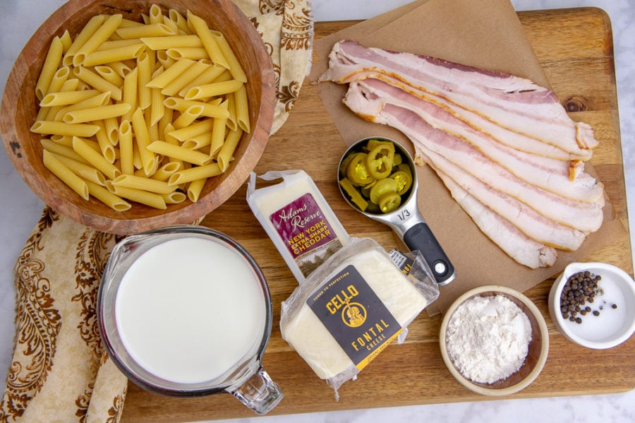 a wooden cutting board with a bowl of pasta, several cheeses, sliced bacon, and cream