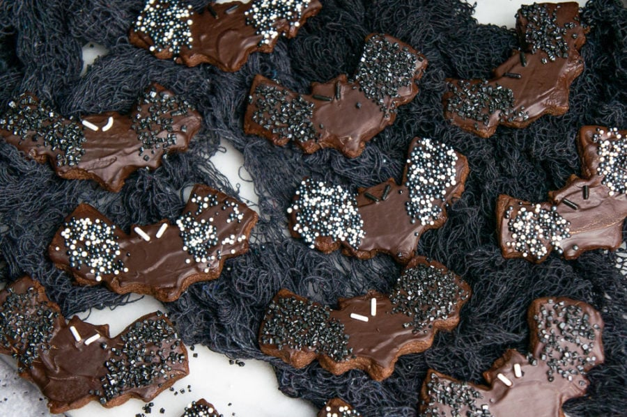 a white granite slab with chocolate bat sugar cookies on black netting