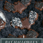Chocolate coated and sprinkled chocolate sugar cookies on a platter with black Halloween netting
