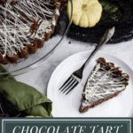 a slice of chocolate tart on a white plate beside the serving platter with the remaining chocolate tart