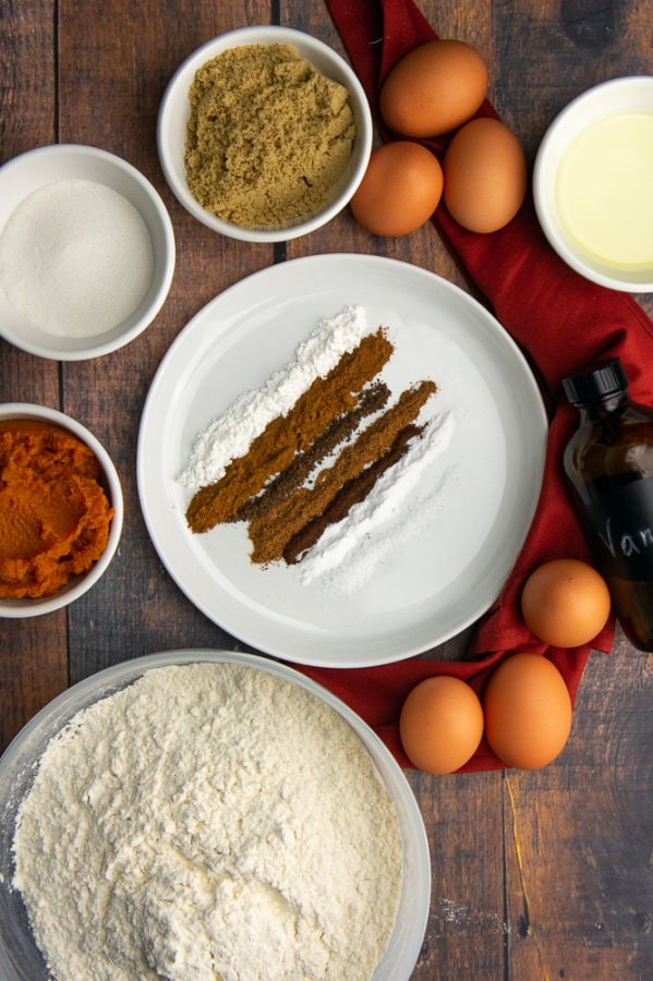 a plate of spices with flour, pumpkin puree, brown and white sugar, eggs, and vanilla