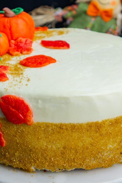 a pumpkin layer cake with gold sprinkles and pumpkin decorations