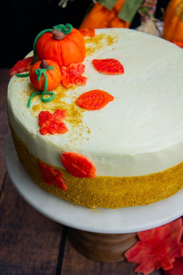 a decorated white frosted pumpkin layer cake with marzipan pumpkins and leaves and gold sprinkles