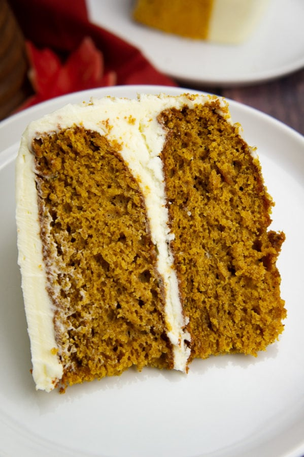 a thick slice of pumpkin layer cake on a white plate