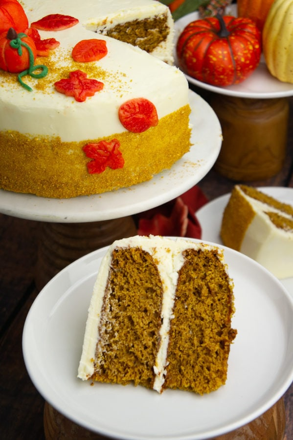 a two layer decorated pumpkin layer cake with a slice set on a white plate