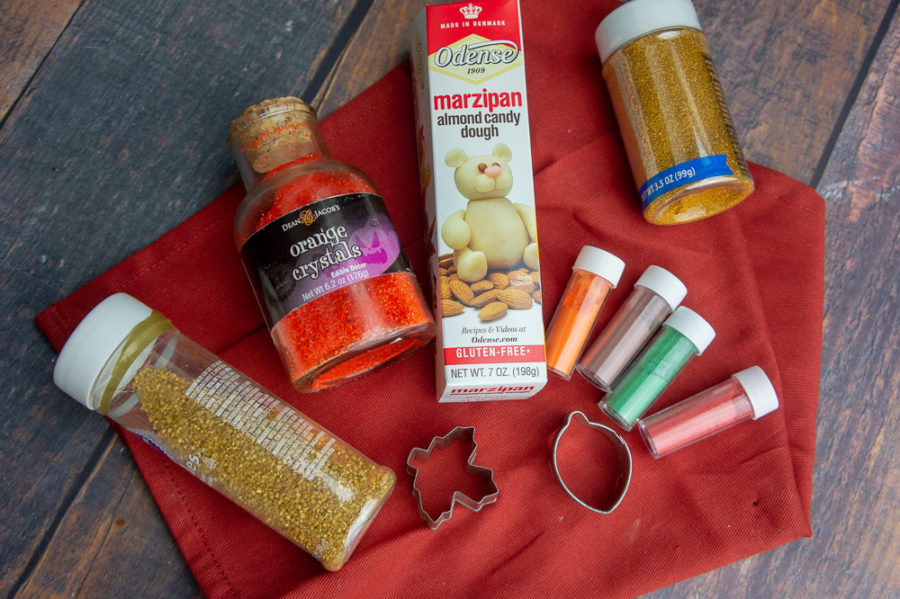 powdered food dye tubes, a box of marzipan and gold sprinkles