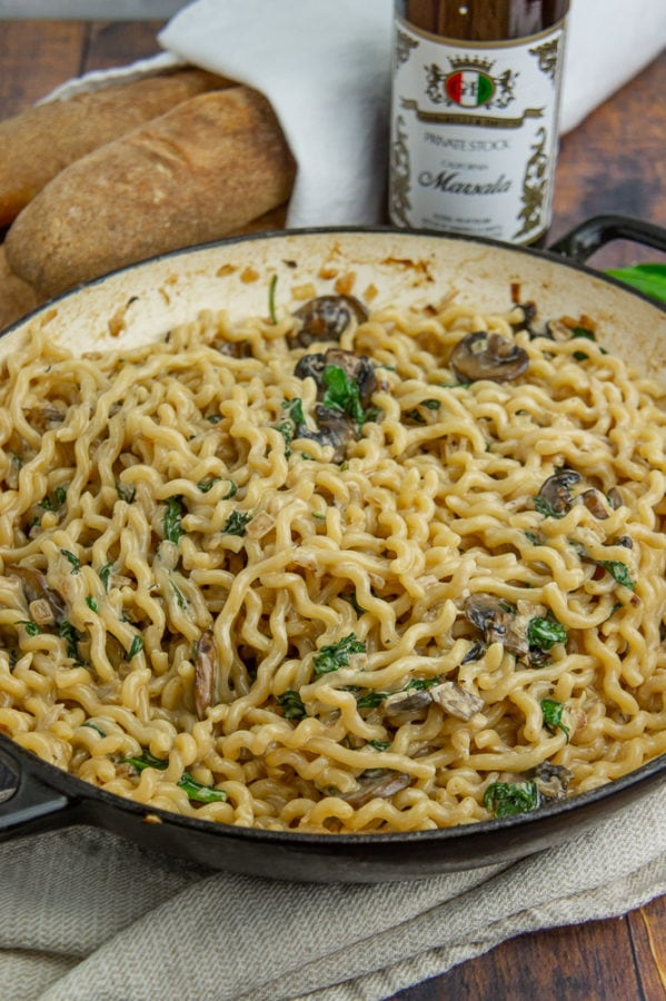 a black pot of pasta with marsala cream sauce next to baguettes