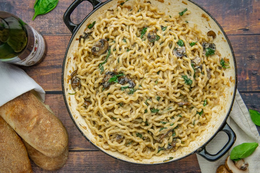 a large pot of wavy noddles with mushrooms and spinach in a creamy sauce beside some baguettes