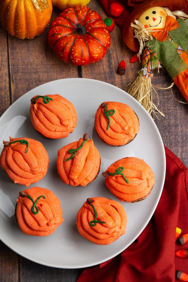 a white platter with pumpkin cupcakes frosted like orange pumpkins with a red napkin and a scarecrow on the table