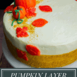 a layer cake with gold sprinkles and marzipan pumpkins and leaves on top.