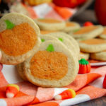 a sugar cookie with a pumpkin in the middle being lifted to reveal an identical one behind it