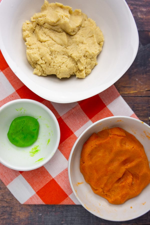 orange dough, green dough, and plain dough in three separate bowls on an orange towel