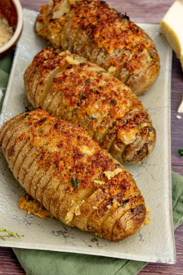 Three russet potatoes roasted hasselback style and topped with browned breadcrumbs and cheese