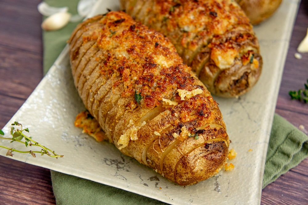 three hasselback potato gratin on a green plate with fresh thyme