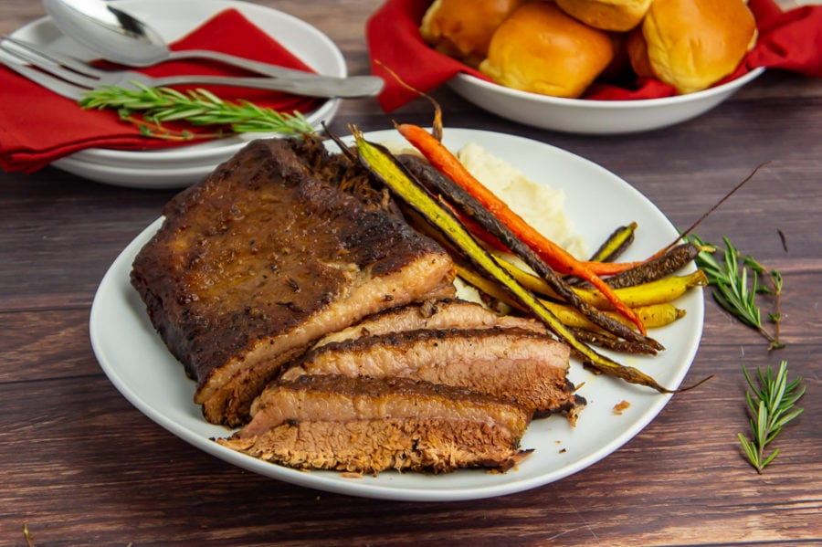 a platter of sliced brisket with roasted carrots on a wooden table