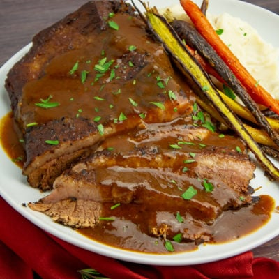 A white platter with sliced braised brisket in red wine sauce next to roasted carrots