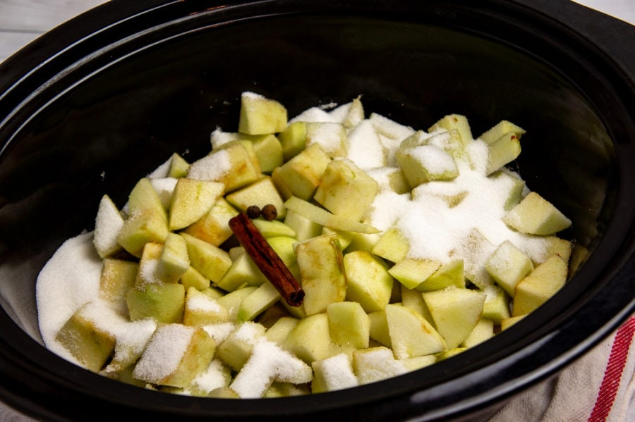 a slow cooker with apples, sugar, and cinnamon