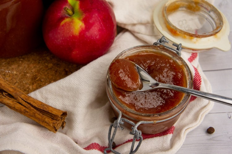 a small jar of apple butter with a spoon scooping some out