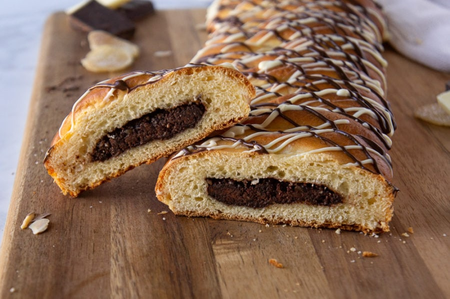 The chocolate filled bread cut open to display the chocolate filling, on a wooden cutting board.