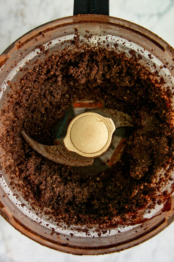 A food processor with a chocolate nut paste blended inside.