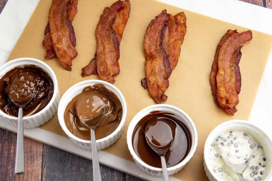 chocolate melted in cups beside cooked strips of bacon