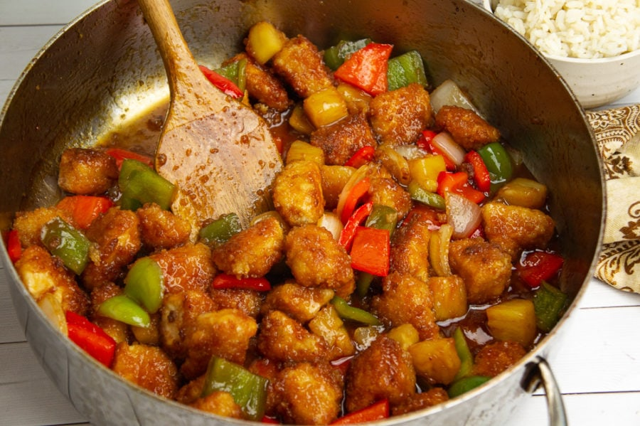 homemade sweet and sour chicken with pineapples and peppers in a large saute pan with a spoon