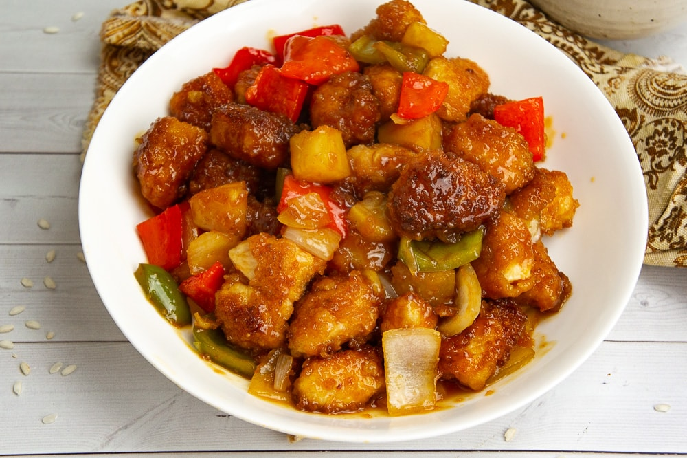 a large white bowl of sweet and sour chicken with pineapple and peppers