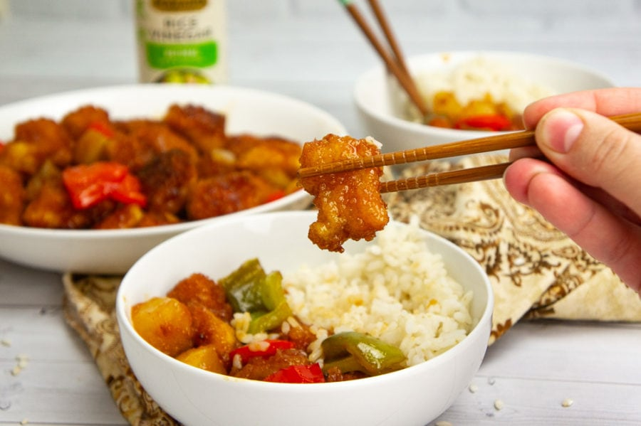 a bowl of sweet and sour chicken with rice and chopsticks picking up a piece of chicken