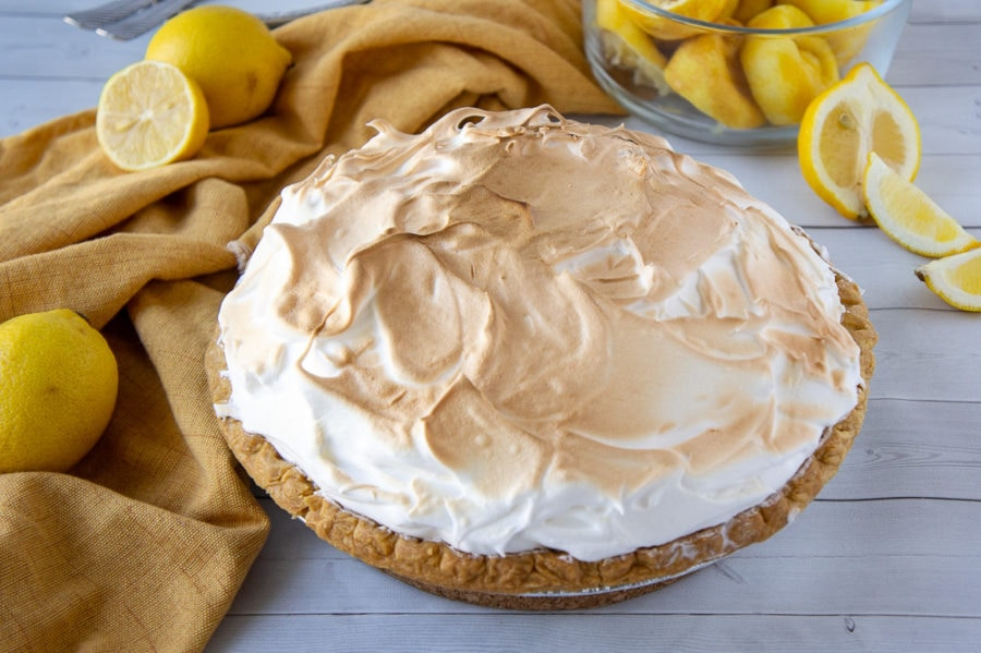 a whole lemon meringue pie on a white wooden table with yellow cloth and lemons