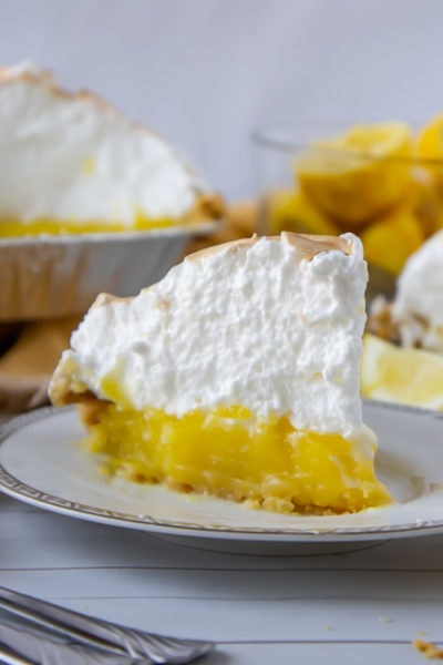 a slice of lemon meringue pie on a white plate with lemons and more pie behind it