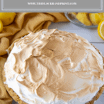 a homemade lemon meringue pie on a white table with a yellow cloth