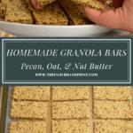 A granola bar being broken in half over a sheet of granola bars