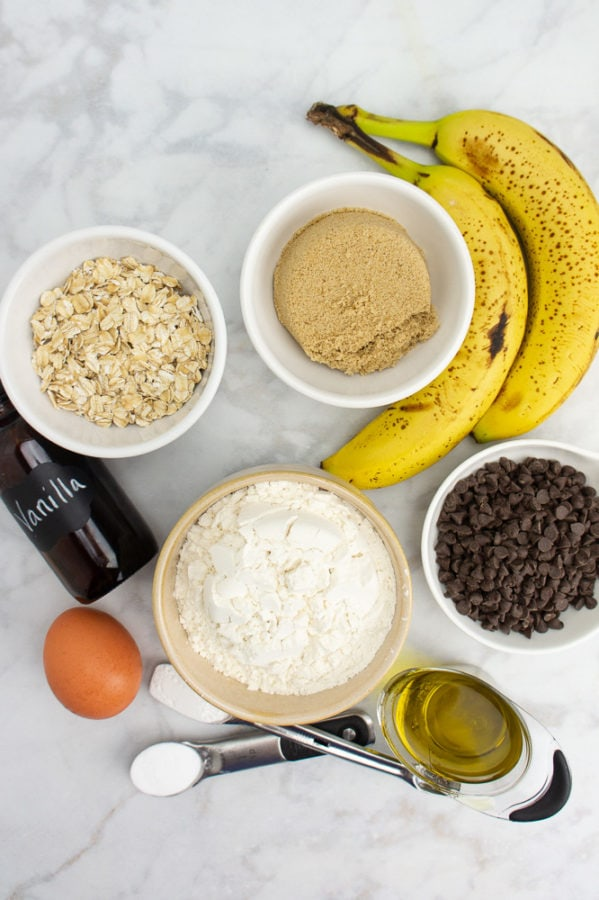 a bowl of white wheat flour beside bowls of oats, sugar, chocolate chips, and two whole bananas